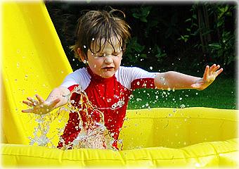 child splashing in pool